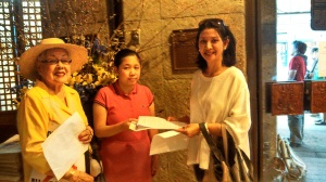 Deputy Consul General Tess de Vega receives the petition from Daphne Ceniza. Lumen Castaneda of the teachers group witnessed the hand-over.